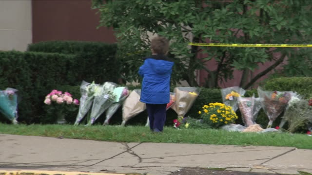 exterior views of a young child laying a floral tribute with his mother outside the tree of life synagogue in the squirrel hill neighbourhood after... - pittsburgh video stock e b–roll