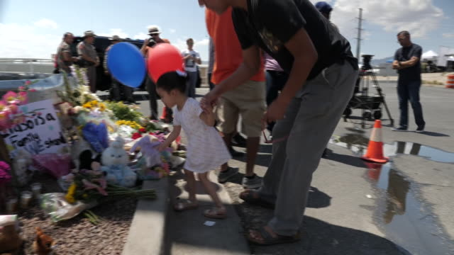 vídeos de stock, filmes e b-roll de exterior views of a young girl and father leaving a tribute at a makeshift memorial on the street near the sight of a mass shooting at a walmart... - tiroteio