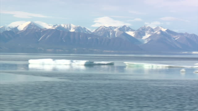 Exterior views of arctic scenery seen from a boat off the coast of Baffin Island looking towards the mountains of the Arctic Cordilleraand views of...
