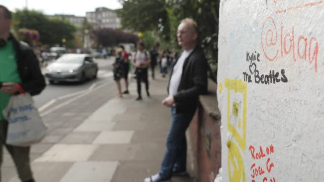 exterior views of beatles graffiti outside abbey road studios and a tv presenter lies in the road on the zebra crossing as press tourists and fans... - zebra crossing stock videos & royalty-free footage
