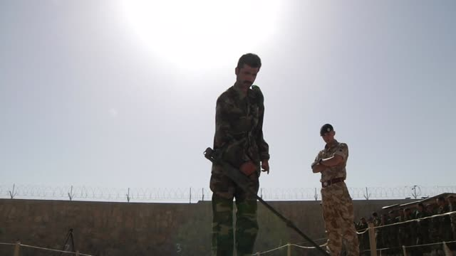 exterior views of britsih army soldiers training an afghan army soldiier in land mine detection using a detector as afghan soldiers look on on 1 june... - land mine stock videos and b-roll footage