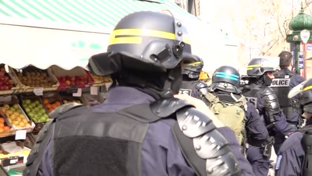 exterior views of crs riot police walking near to the marching yellow vest protesters on 23 march 2019 in paris france - waistcoat stock videos & royalty-free footage