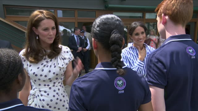 Exterior views of Duchess Of Sussex and Duchess Of Cambridge meeting and greeting ball boys and girls and tennis players at the Wimbledon Lawn Tennis...