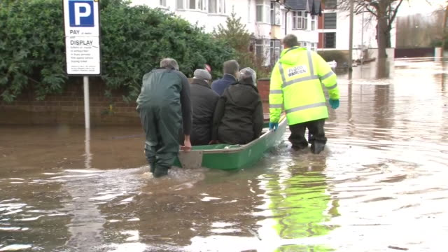 exterior views of flooding damage caused by storm dennis including a people being taken to safety on a boat in a suburban street with a flood sign in... - storm stock videos & royalty-free footage