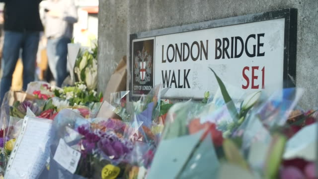exterior views of flowers and tributes, including one from the merritt family, at the scene of the london bridge terror attack to the victims on 2... - terrorism stock videos & royalty-free footage