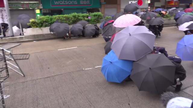 """exterior views of hong kong riot police holding up a red warning banner """"disperse or we fire"""" and then tear gas is fired at protesters from a subway... - danger stock videos & royalty-free footage"""