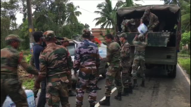 stockvideo's en b-roll-footage met exterior views of indian soldiers delivering supplies of water towels and food parcels to flood victims on 21st august 2018 in kerala india - slachtoffer