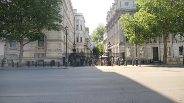 exterior views of number 10 downing street seen through a wire fence, and security guarding the gates and a union jack flying against clear blue sky... - gate stock videos & royalty-free footage