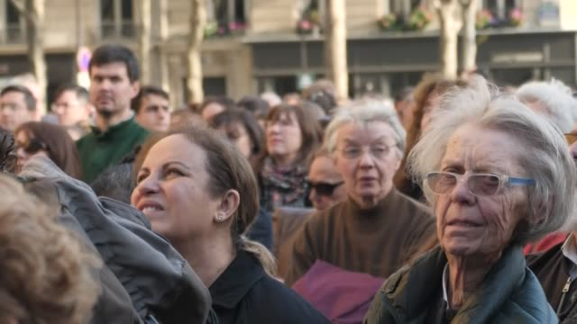 exterior views of people gathered in the square in front of the church of saint sulpice as bells ring out to honour notre dame cathedral after the... - gottesdienst stock-videos und b-roll-filmmaterial