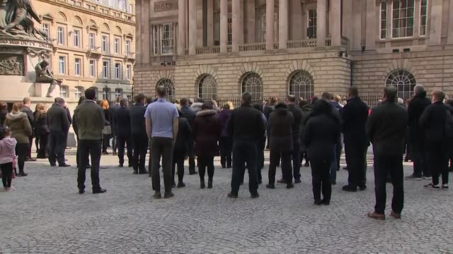 exterior views of people observing a period of silence as bells ring in exchange flags square opposite liverpool town hall as it marks 30 years since... - hillsborough disaster stock videos and b-roll footage