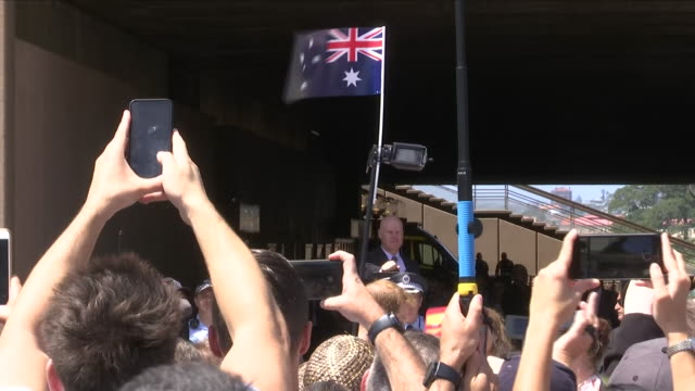 Exterior views of people taking photos and straining to see Prince Harry and Meghan The Duke and Duchess of Sussex on a walkabout in Sydney on...