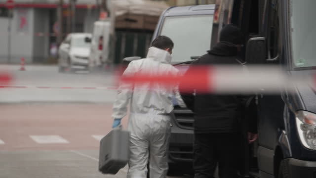exterior views of police activity including officers in forensic suits and crime scene cordon tape at the scene of the shootings at shisha bars on 20... - ロープ仕切り点の映像素材/bロール