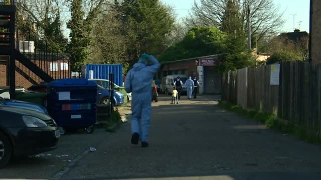 vídeos de stock e filmes b-roll de exterior views of police at stabbing crime scene in pinner showing police forensic squad walking down an alleyway behind houses shops on 24 march... - gangue