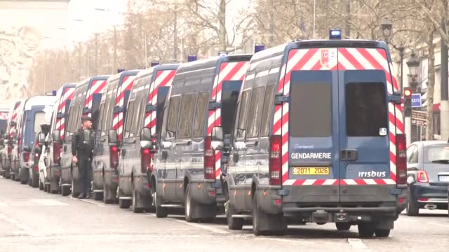 vídeos de stock, filmes e b-roll de exterior views of police gathering on avenue des champs elyseesand a line of gendarmerie vans driving and parked in view of the arc de triomphe in... - vest