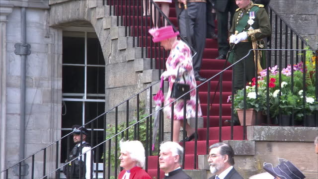Exterior views of Queen Elizabeth II arriving as the host of her annual summer garden party at Holyrood Palace including walking down steps and being...