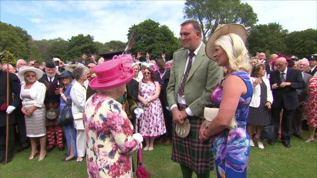exterior views of queen elizabeth ii being introduced and talking to to ex rugby player doddie weir and his wife kathy at the annual summer garden... - scozia video stock e b–roll