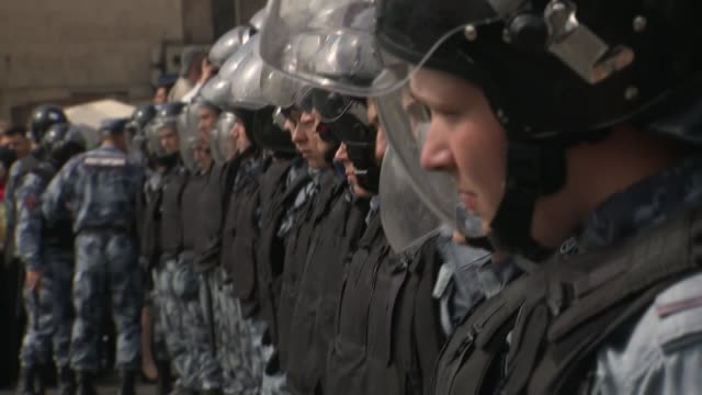 vidéos et rushes de exterior views of riot police lined up as they keep watch on a protest arresting and a lady demonstrating with them on 3 august 2019 in moscow, russia - moscou
