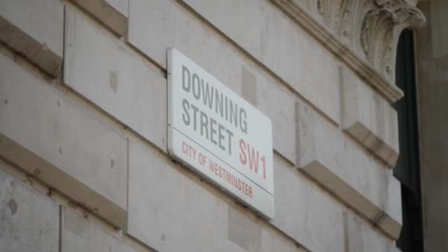 exterior views of street signs for downing street and whitehall seen next to each other above the gates to downing street in westminster on 28 may... - road sign stock videos & royalty-free footage