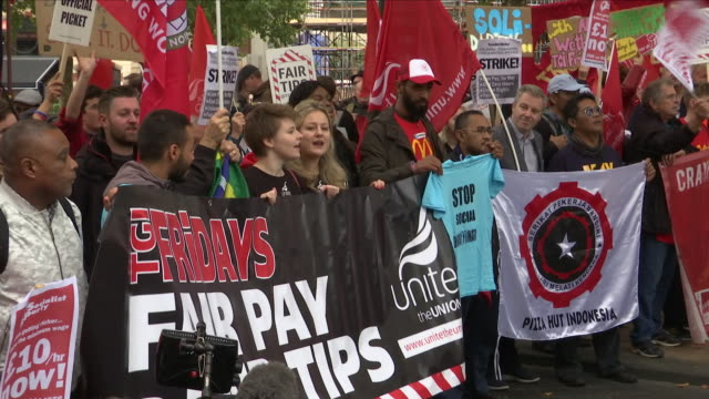 Exterior views of striking hospitality workers in a protest rally outside a branch of McDonalds chanting and waving flags and banners on October 04...