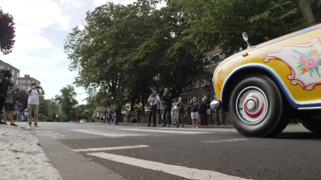 exterior views of the arrival of a beatles yellow rolls royce on the 50th anniversary of the iconic abbey road photo as media and press gather to... - rolls royce stock videos & royalty-free footage
