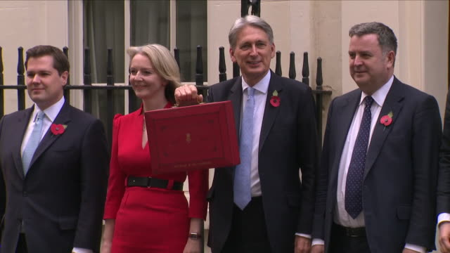 exterior views of the chancellor phillip hammond stepping out from 11 downing and showing his red briefcase for the classic budget photocall standing... - briefcase stock videos & royalty-free footage