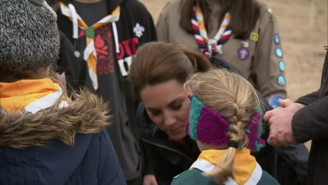 Exterior views of The Duke and Duchess of Cambridge talking and laughing with volunteers school pupils and loca scouts as they prepare to help with a...