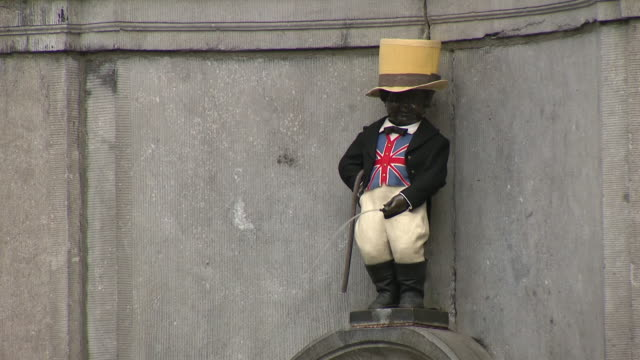 exterior views of the famous manneken pis statue dressed in a hat and union jack waistcoat as tourists walk past in brussels belgium on 30 january... - waistcoat stock videos & royalty-free footage
