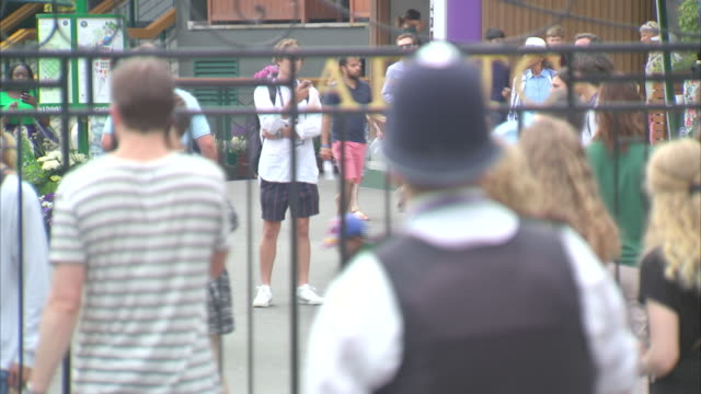 Exterior views of the front gates of Wimbledon All England Lawn Tennis Club including crowds and a policeman watching on 8 July 2019 in Wimbledon...