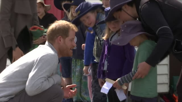 exterior views of the maranui cafe in lyall bay as prince harry and megan the duke and duchess of sussex talk with a group of small children as they... - ロイヤルツアー点の映像素材/bロール