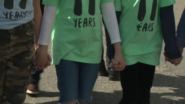 exterior views of the mothers rise up climate change action march, including young children holding hands at the front of the march and all wearing... - all shirts stock-videos und b-roll-filmmaterial