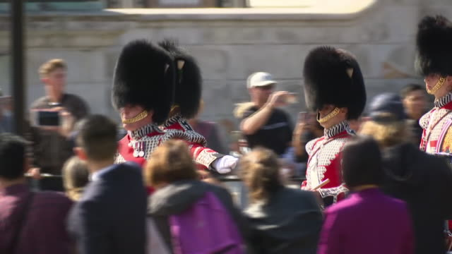 exterior views of the queen's guards marching and parading outiside bukingham palace in front of a large crowd of tourists, including household... - british military stock-videos und b-roll-filmmaterial