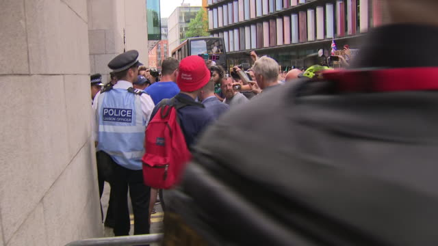 exterior views of tommy robinson being led away from the old bailey by police as a media scrum of press journalists and supportrers surround him... - umgeben stock-videos und b-roll-filmmaterial