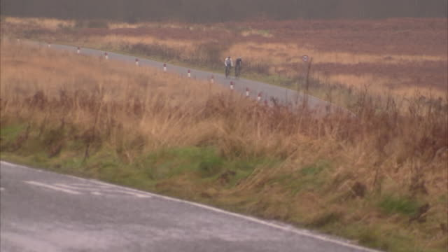 Exterior views of two cyclists riding in the Yorkshire Dales in the rain on December 14 2012 in UNSPECIFIED United Kingdom