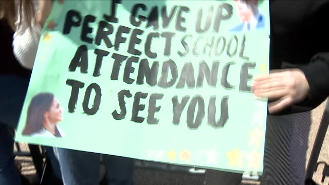 Exterior views of two young fans holding up posters they made to welcome for Prince Harry and Meghan The Duke and Duchess of Sussex to Sydney after...