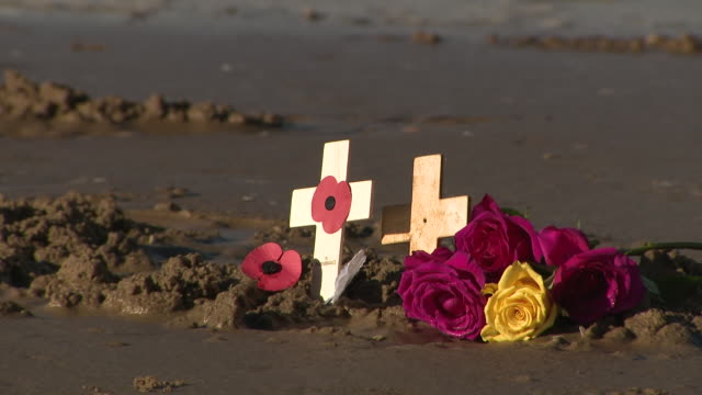 exterior views of waves washing away the sand art portrait of john basil armitage on formby beach including poppy remembrance cross and wreath on 11... - kranz stock-videos und b-roll-filmmaterial