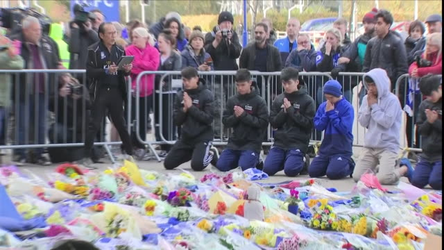 """exterior views of what is believed to be the thai cave rescue football team """"the wild boars"""" kneeling and pay tribute outside leicester city's king... - football team stock videos & royalty-free footage"""