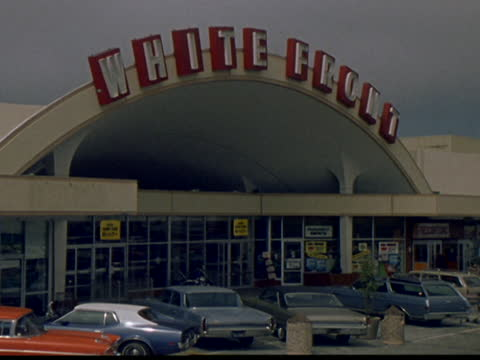 1971 exterior views of white front discount department store and parking lot - メガストア点の映像素材/bロール