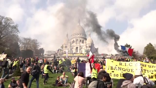 vídeos de stock, filmes e b-roll de exterior views of yellow vest protesters as they gather at the base of sacre coeur in montmatre and sing the french national anthem including flare... - vest
