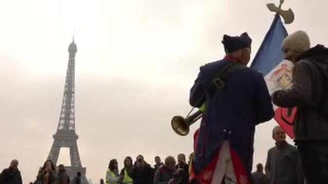 exterior views of yellow vest protesters gather at the place de trocodero with the eiffel tower in the background on 23 march 2019 in paris france - waistcoat stock videos & royalty-free footage