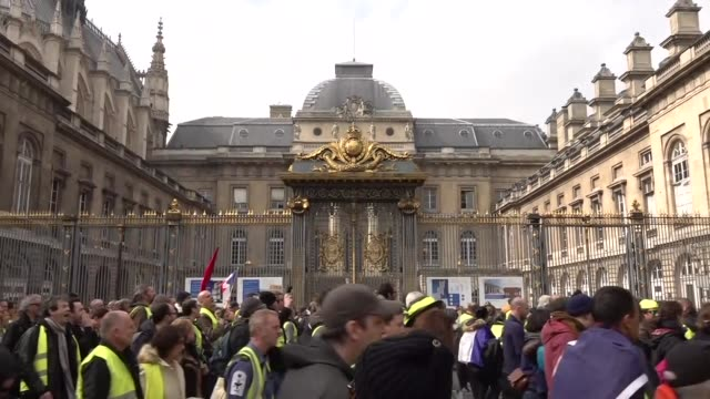 exterior views of yellow vest protesters marching and chanting and carrying flags as they they march past the palais de justice de paris on 23 march... - waistcoat stock videos & royalty-free footage