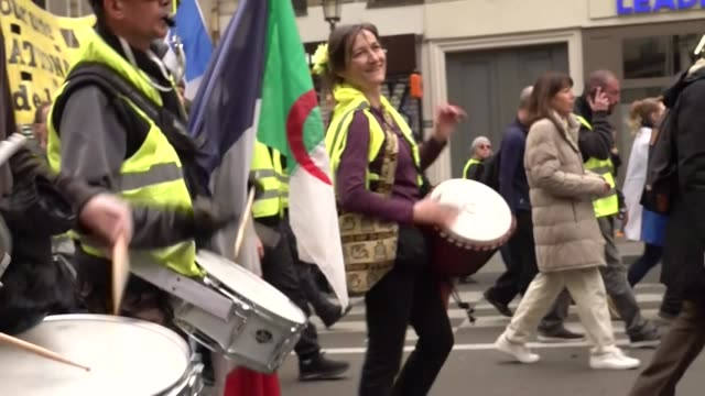 vídeos de stock, filmes e b-roll de exterior views of yellow vest protesters marching and chanting as they play drums and carrying large protest banners on 23 march 2019 in paris france - vest