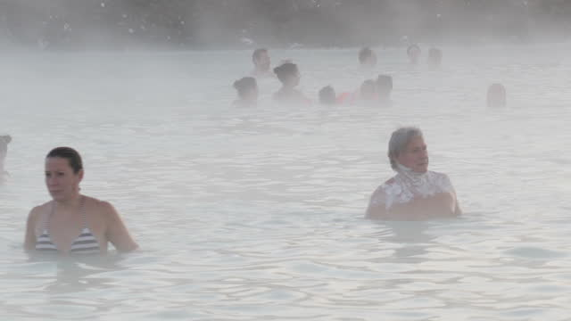 Exterior wide arty shots of people swimming in the Blue Lagoon Geothermal Spa baths tourist attraction men and women some wearing face masks mist in...