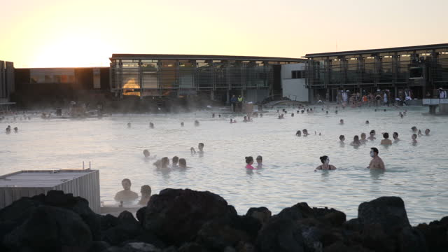Exterior wide arty shots of people swimming in the Blue Lagoon Geothermal Spa baths tourist attraction men and women some wearing face masks mist and...