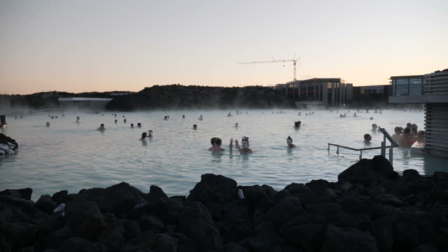 Exterior wide pan of arty shots of people swimming in the Blue Lagoon Geothermal Spa baths tourist attraction men and women some wearing face masks...