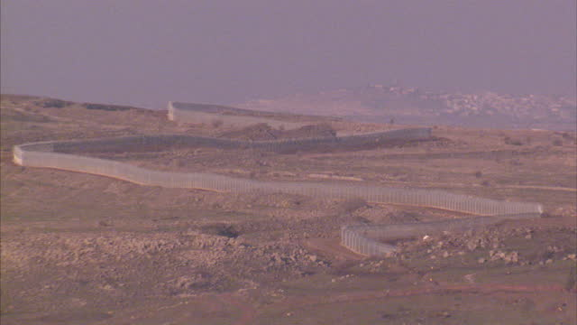 exterior wide shot israeli separation barrier fence threading up hillside on golan heights on january 26 2014 in safed israel - boundary stock videos & royalty-free footage
