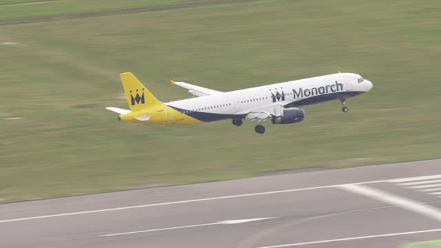 Exterior wide shot of a Monarch plane landing on the runway at Gatwick Airport on September 26 2016 in London England