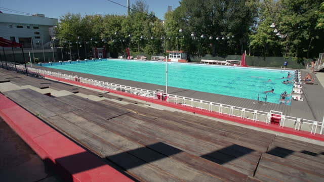 exterior wide shot of an outdoor swimming pool in bucharest romania on a hot sunny summer day side views and front views of young caucasian male... - swimming trunks stock videos & royalty-free footage