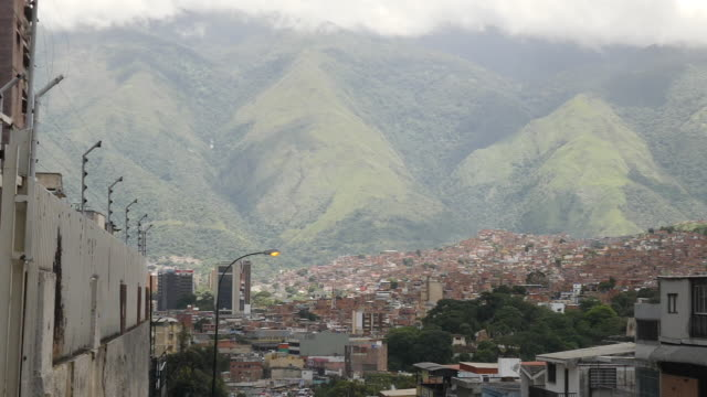 exterior wide shot of caracas citizens walking uphill along the street with wide view of the mountains overlooking the venezuelan city these shots... - uphill stock videos & royalty-free footage