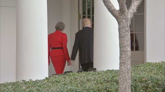 Exterior wide shot of President Donald Trump and Prime MinisterTheresa May walking through the White House gardens holding hands briefly before...