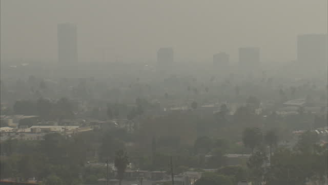 exterior wide shot panning across the smog shrouded skyline of downtown los angeles.>> on november 01, 2017 in los angeles, california. - smog stock-videos und b-roll-filmmaterial